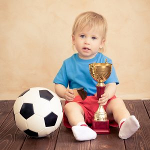 Child is pretending to be a soccer player. Success and winner concept