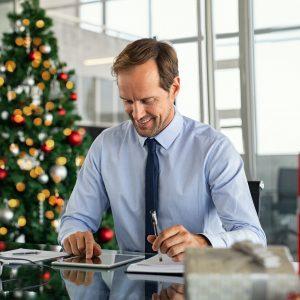 Businessman working on digital tablet at christmas