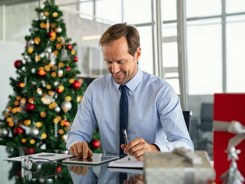 Businessman working on digital tablet at christmas