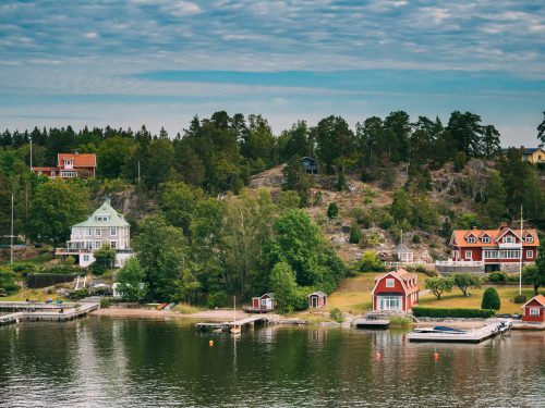 Sweden. Many Beautiful Red Swedish Wooden Log Cabins Houses On Rocky Island Coast In Summer Sunny Evening. Lake Or River Landscape.